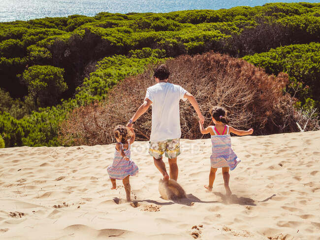 Back view of anonymous father with his two daughters walking on sand dune on a bright summer day — Stock Photo
