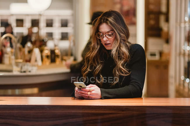 Thoughtful female using smartphone in cafe — Stock Photo