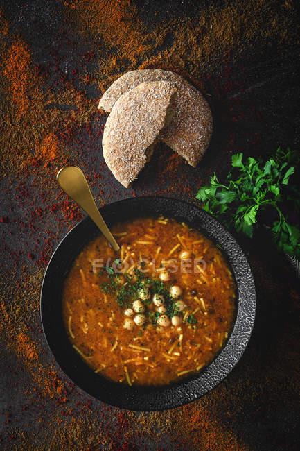 Soupe traditionnelle Harira pour Ramadan dans un bol à la surface sombre avec du pain et de la coriandre — Photo de stock