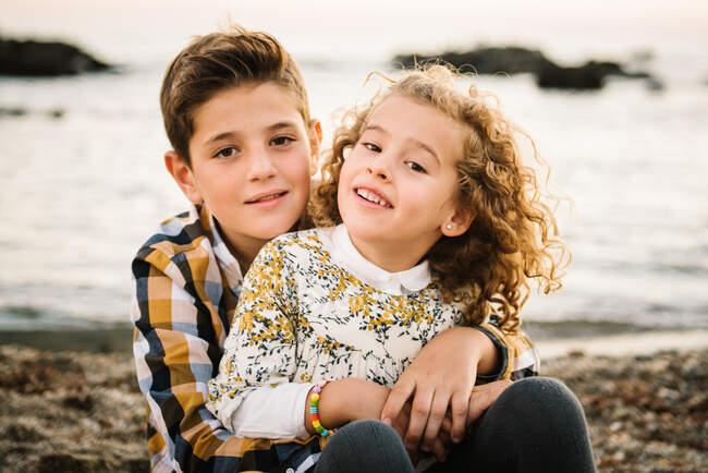 Веселые и симпатичные мальчик и девочка улыбаются и обнимают друг друга на пляже — стоковое фото