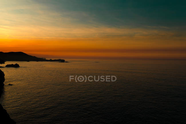 Minimalist landscape of calm rippled water of ocean with colorful sky at sunset, Spain — Stock Photo