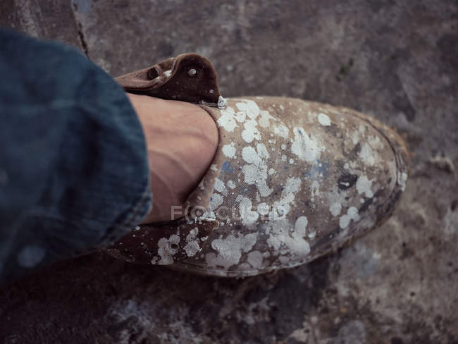 Foot of anonymous artist in dirty shoe covered with stains of paint on floor of workshop — Stock Photo