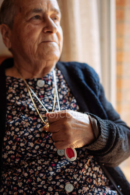 Elderly woman with personal alarm hanging from the neck — Stock Photo