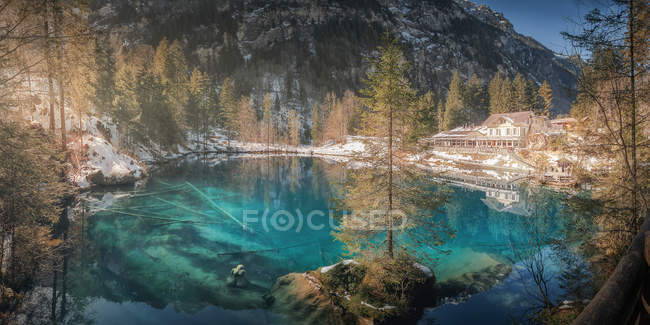 Landscape of peaceful azure lake with snowy shore and resort building in mountains of Switzerland — Stock Photo