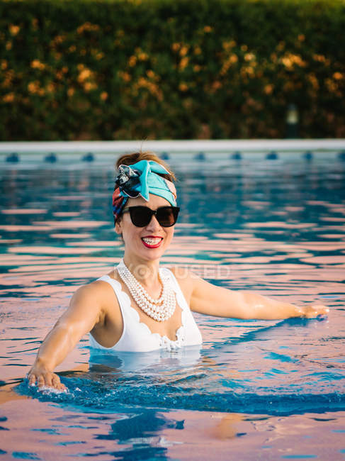 Young rich chinese woman relaxing swimming in a pool at a luxurious resort — Stock Photo