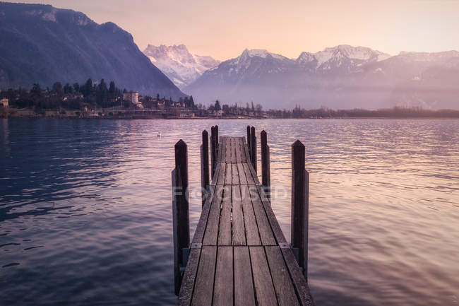 Wood pier above turquoise lake in snowy mountains at sunset of Switzerland — Stock Photo