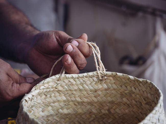 Hands of anonymous artisan holding basket braided from dried palm fiber — Stock Photo
