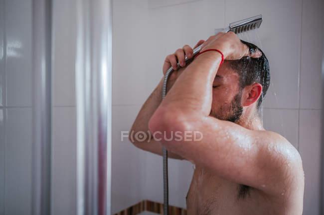Shirtless unrecognizable man having shower in bathroom — Stock Photo