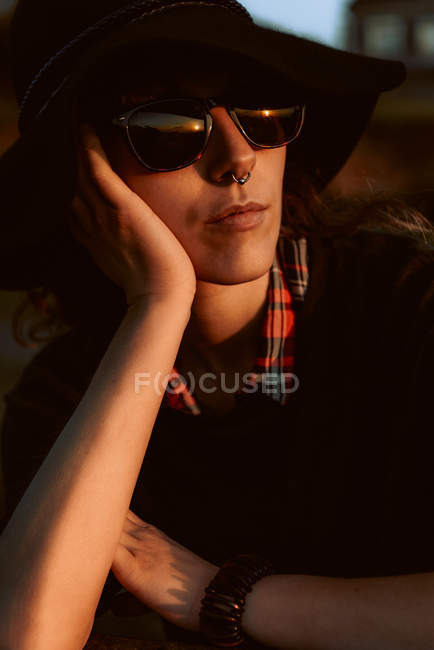 Donna pensierosa che indossa occhiali da sole alla moda con cappello nero appoggiato a portata di mano alla luce del sole — Foto stock