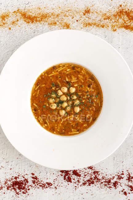 Sopa tradicional de harira para Ramadan na placa no tabletop branco com especiarias dispersadas — Fotografia de Stock
