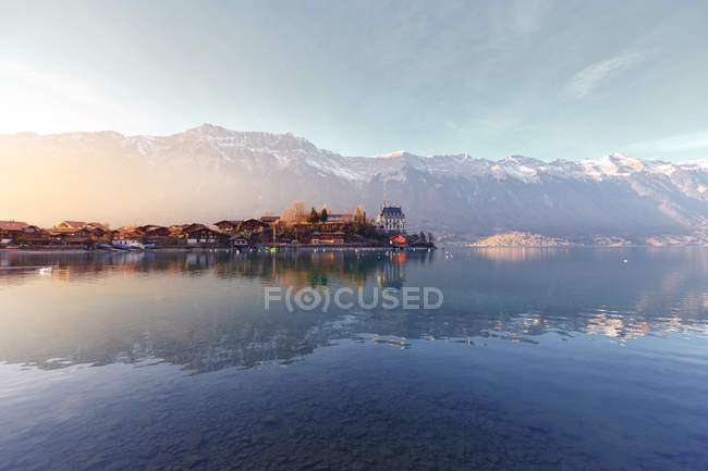 Landscape of peaceful blue lake with houses on shore at sunset on background of mountains in sunshine, Switzerland — Stock Photo