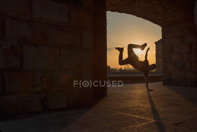 Irreconocible adolescente haciendo handstand en arco de viejo edificio mientras romper bailando en la calle de la ciudad durante la puesta del sol - foto de stock