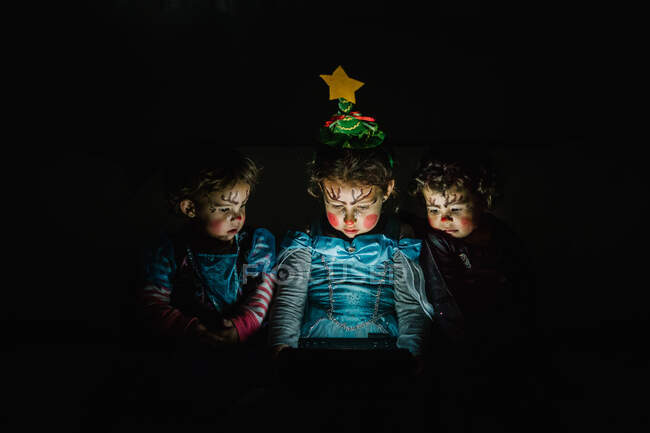 Три милі дівчатка з костюмами принцеси дивляться на дисплей комп'ютера на чорному тлі. — стокове фото