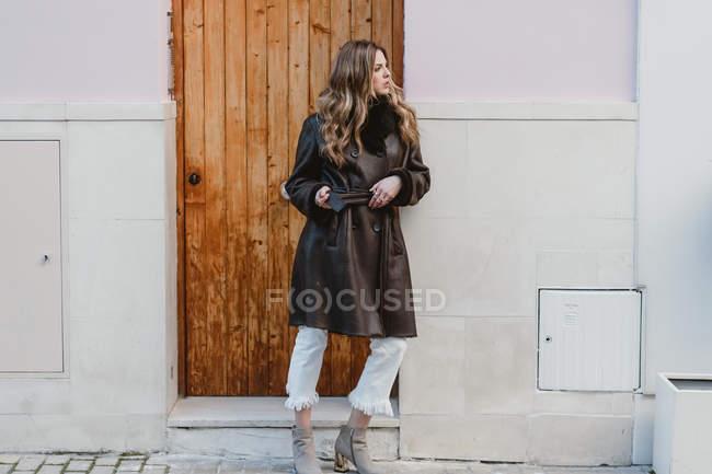 Stylish woman in vintage leather coat standing near wooden door on street — Stock Photo