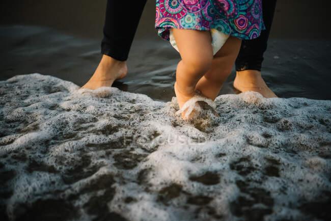 Mãe segurando criança andando — Fotografia de Stock