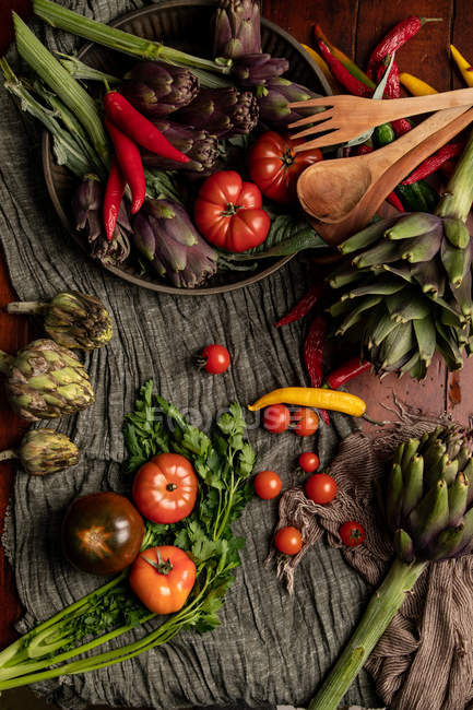 Set mit verschiedenen frischen Gemüse und Stoffservietten rustikal auf dem Tisch in der Küche — Stockfoto