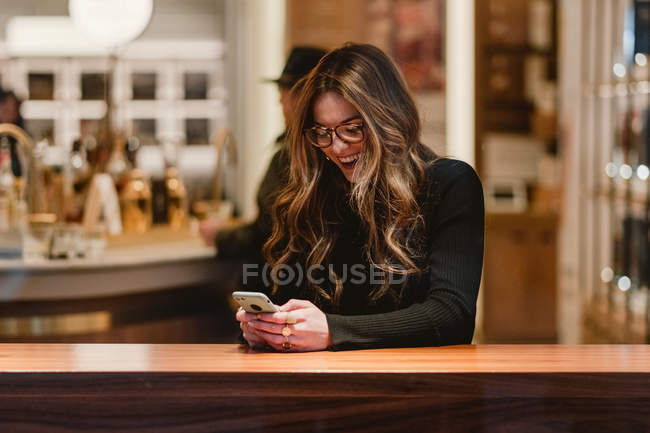 Pretty lady in trendy outfit laughing and browsing modern smartphone while sitting at table in stylish cafe — Stock Photo