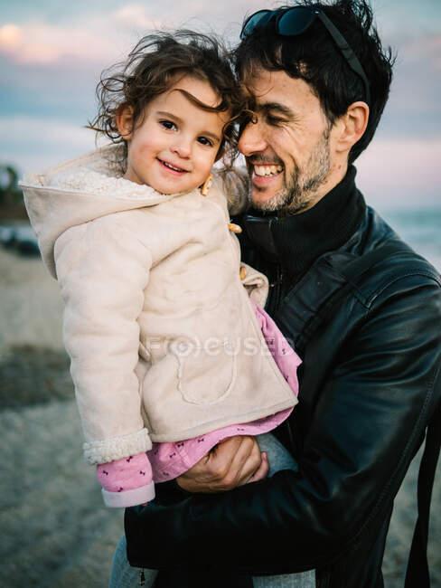 Гарна сцена, коли тато тримає і обіймає свою маленьку дочку на пляжі взимку. — стокове фото