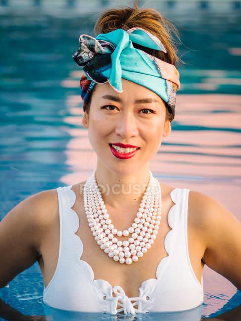 Молодая богатая китаянка расслабляется в бассейне на роскошном курорте — стоковое фото