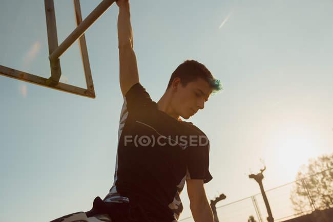 Підліток висить позаду баскетбольне кільце — стокове фото