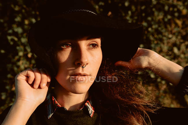 Young sensual brunette wearing black hat and accessories while posing in sunlight — Stock Photo