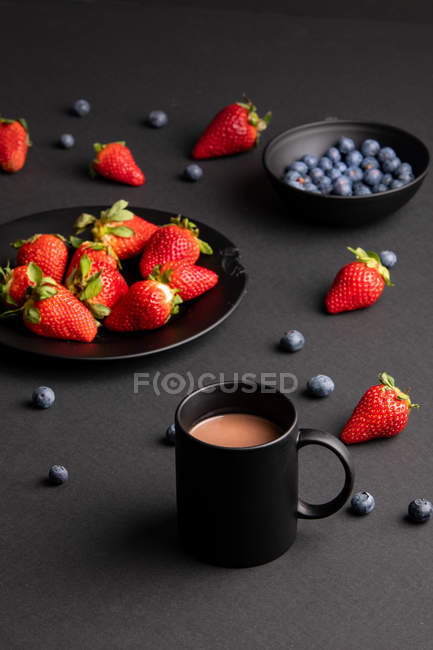 Various fresh berries and mug of aromatic hot beverage for breakfast on black background — Stock Photo
