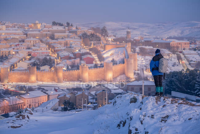 Back view of traveler admiring picturesque view of illuminated snowy town against twilight sky background — Stock Photo