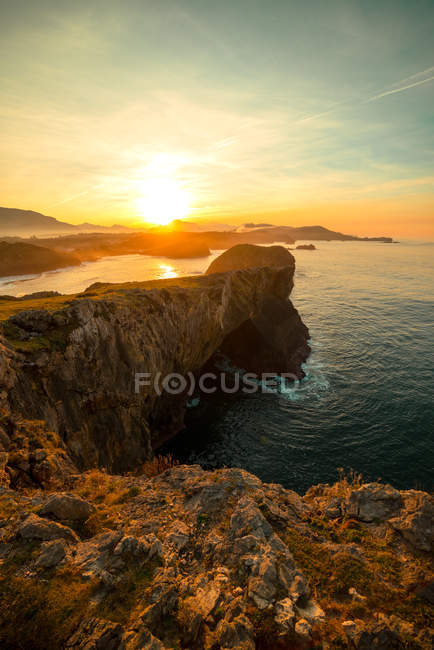 Panoramic view of huge rocky cliffs above rippled water against sunset sky, Asturias, Spain — Stock Photo