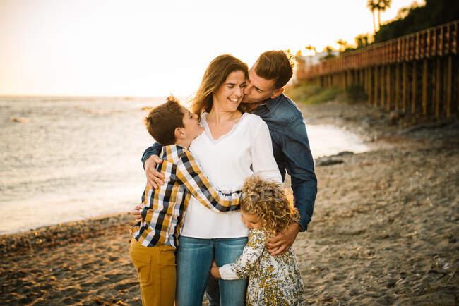 Чоловік середнього віку, жінка з дітьми на березі моря посміхається і обіймає один одного — стокове фото