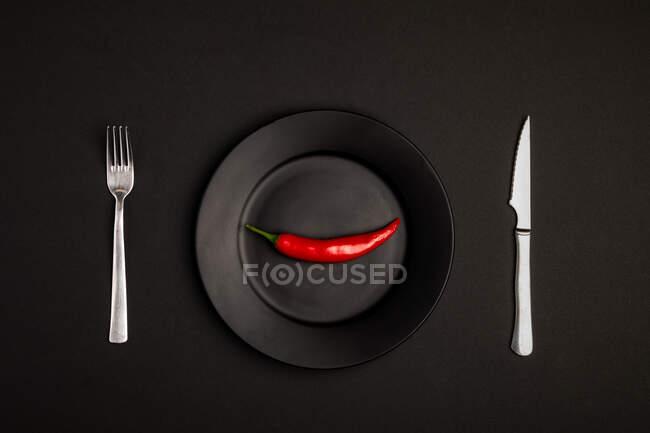 Garfo e faca colocados no fundo preto perto da placa com chili peeper fresco — Fotografia de Stock