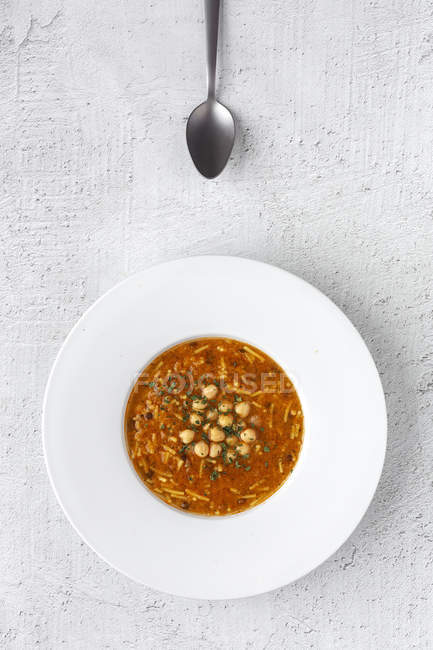 Soupe traditionnelle Harira pour Ramadan dans une assiette sur une table blanche avec cuillère — Photo de stock
