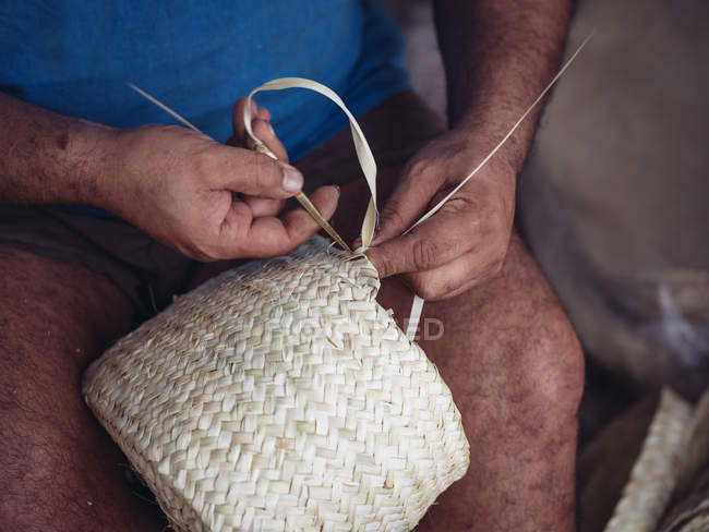 Hands of anonymous artisan weaving lovely basket with braided dried palm fiber — Stock Photo