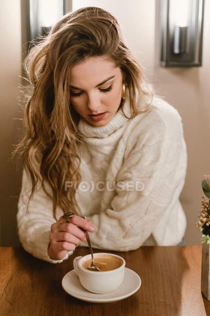 Елегантна жінка, яка змішує каву в кафе. — стокове фото