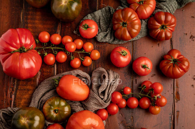Assorted fresh tomatoes and fabric napkins on lumber tabletop in kitchen — Stock Photo