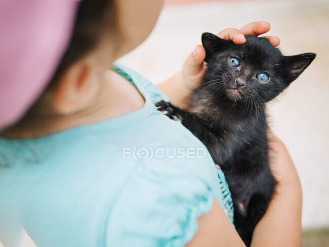 Tender scene of cute little girl holding and rocking a small black pussycat — Stock Photo