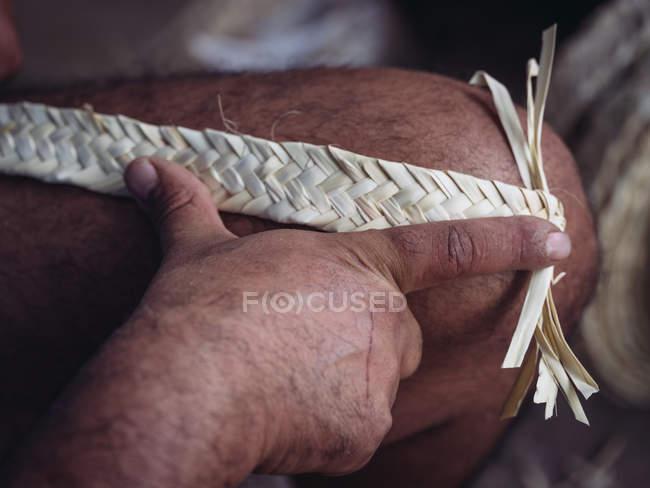 Mão de artesão anônimo usando gancho para tecer folhas de palma secas de fibra enquanto trabalhava na oficina — Fotografia de Stock