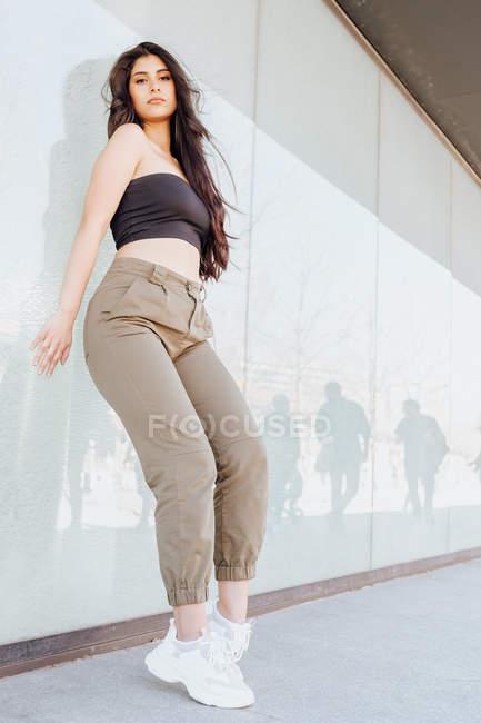 Beautiful woman standing near wall — Stock Photo