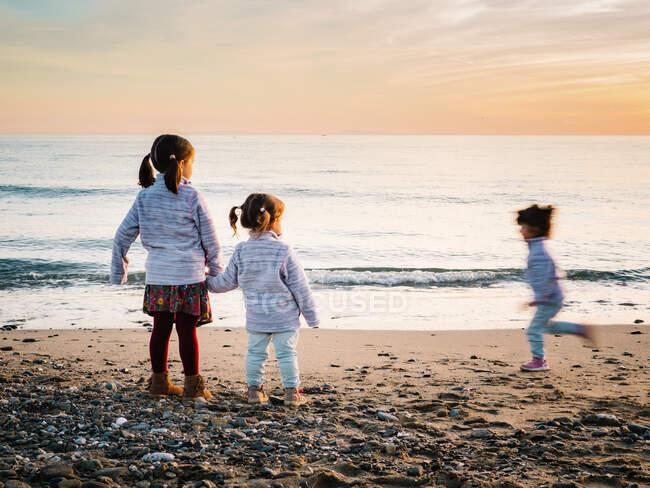 Niñas pequeñas cogidas de la mano mientras otra hermana corre en la playa en un día de invierno - foto de stock