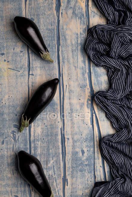 Berenjenas frescas maduras esparcidas cerca de un trozo de tela rayada sobre una mesa de madera envejecida - foto de stock