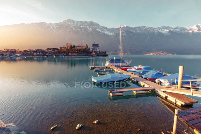 Landscape of peaceful blue lake with small pier and boats on background of mountains in sunshine, Switzerland — Stock Photo