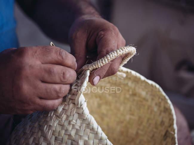 Руки анонімних ремісника плетіння прекрасної корзини з плетеними сушеними пальмовими волокном — стокове фото