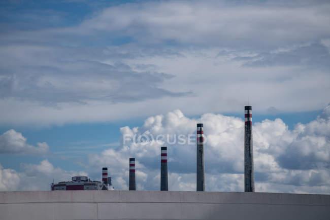 Impilamenti industriali di scarico in fila dietro parete grigia su sfondo di cielo pittoresco nuvoloso — Foto stock