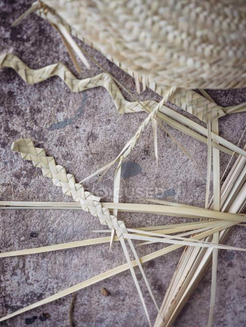 Trançado folhas de palma secas de fibra no chão de cimento grungy — Fotografia de Stock