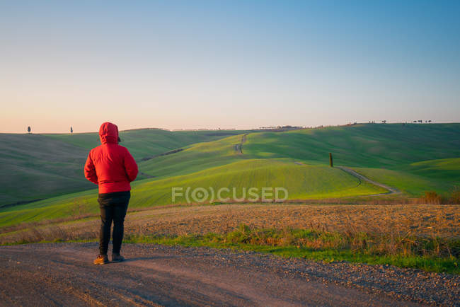 Person in jacket standing on empty rural road in majestic green fields of Italy — Stock Photo