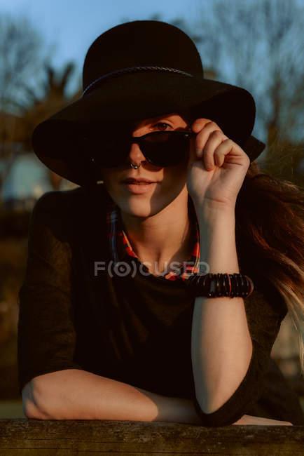 Femme pensive utilisant des lunettes de soleil à la mode avec le chapeau noir se penchant sur la main et regardant l'appareil-photo dans la lumière du soleil — Photo de stock