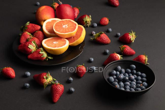 Divers fruits et baies frais dispersés sur le fond noir — Photo de stock