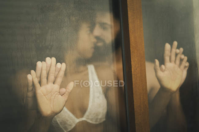 Handsome Hispanic guy touching and kissing seductive African American woman in lace bra while standing behind wet window — Stock Photo