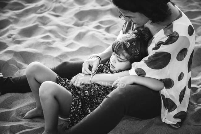 Мама сидить з донькою на пляжі. — стокове фото