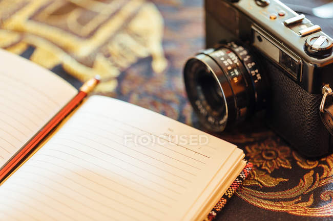 Closeup of open notebook next to a vintage camera on decorative table — Stock Photo