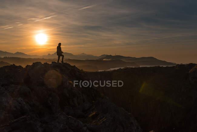 Silhouette of traveler standing on cliff of seashore against sunset sky, Spain — Stock Photo